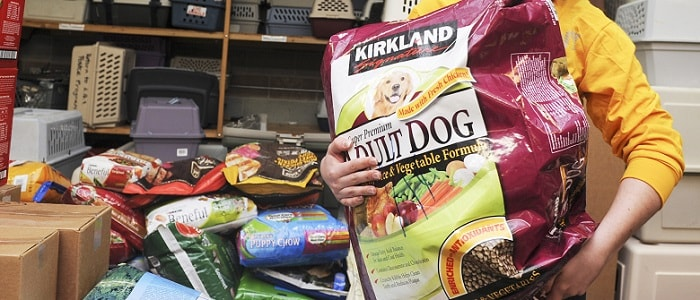 a woman holding a large bag of Kirkland dog food